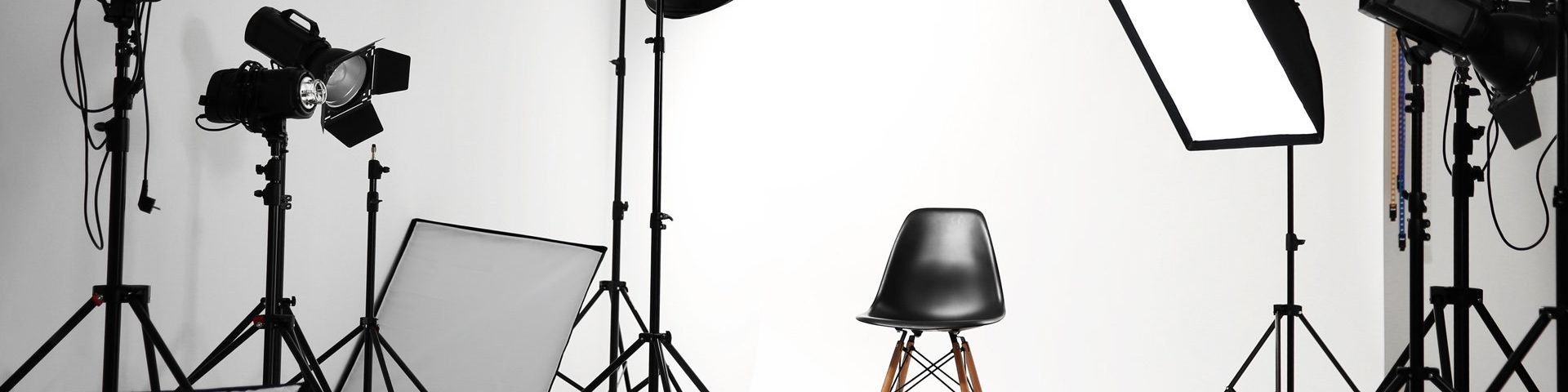 A black chair in the middle of a white photography studio, surrounded by lights.